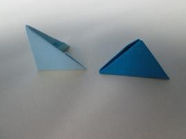 1. Îmbinăm primele module ale coşuleţului. Un picioruş al unei piese aşezate sub forma unui triunghi dreptunghiular va fi introdus în buzunăraşul altei piese aşezate sub forma unui triunghi echilateral.